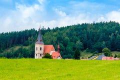 Славная средневековая церковь за лугом Лес на предпосылке, голубом s Стоковая Фотография