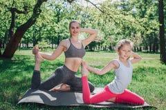 Славная съемка девушек excercising совместно Они сидят на левых ноге и stretchin правое одно с правой рукой alric стоковое изображение rf