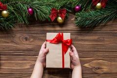 Славная тема рождества на деревянной предпосылке с ветвями сосны на верхней части экрана Подарок на рождество в Стоковые Фото