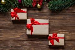 Славная тема рождества на деревянной предпосылке с ветвями сосны на верхней части экрана Настоящий момент кладет диагональ в коро Стоковая Фотография