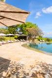 Славная тропическая сторона бассейна с зонтиком солнца und солнц-loungers, vert Стоковая Фотография RF