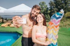 Славное изображение бородатого парня и крепкой девушки стоя и представляя на камере Они принимают selfie на телефоне Улыбка людей стоковое фото