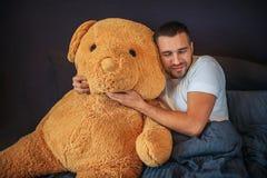 Славное изображение взрослого с большой оранжевой игрушкой медведя Гай обнимает и полагается к нему Он держит глаза закрытый Чело стоковая фотография rf