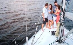 Славное изображение 4 людей стоя на яхте Брюнет смотрит парня Она усмехается Он обнимает ее другие пары стоковая фотография