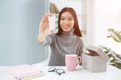 Славное изображение привлекательной девушки сидя на таблице и показывая продукт красоты к камере Это сливк руки Стоковые Изображения