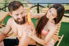 Славное изображение тщательной девушки сидит за парнем и положило некоторую сливк sunproof из оранжевой бутылки она держит в руке стоковая фотография
