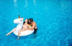 Славное и положительное изображение заплывания человека и женщины в бассейне Девушка сидит на тюфяке воздуха Она смеется над Стой стоковая фотография rf