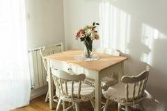 Славно украшенная живущая комната Обеденный стол и некоторые стулья стоковые фото