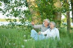 Славные зрелые пары сидя на зеленой траве стоковое изображение