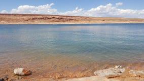 Славные камешки около голубого озера стоковые изображения rf