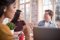 Славные молодые коллеги говоря друг к другу Стоковые Изображения