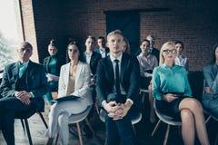 Славные стильные элегантные уверенные акулы менеджеров высшего звена сидя на стульях слушая финансы запуска босса CEO (главный ис стоковое фото rf