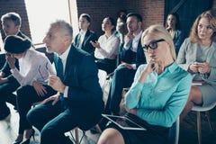 Славные bossy занятые стильные элегантные серьезные акулы присутствуя на форуме слушая CEO (главный исполнительный директор) конф стоковая фотография