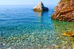 Славный взгляд моря Штиль на море берегом Очистите Pebble Beach и большие камни Адриатическое море Черногория Стоковая Фотография