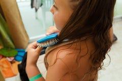 Славный взгляд со стороны крупного плана маленькой девочки держа гребень или щетку и чистя ее длинные волосы щеткой внутри комнат Стоковые Фото