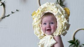 Славный младенец нося желтый головной убор представляет на камере на крупном плане photoshoot сток-видео