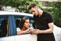 Славный парень с правильным направлением находки порции телефона к красивой женщине Используя Smartphone стоковые изображения rf