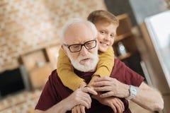 Славный пожилой человек держа его руки внуков стоковые изображения rf
