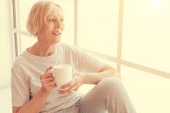 Славный постаретый чай женщины выпивая на силле окна Стоковая Фотография