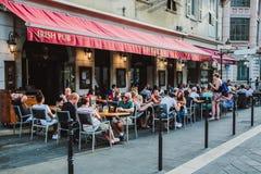 СЛАВНЫЙ, ФРАНЦИЯ - 26-ОЕ ИЮНЯ 2017: вне традиционного ресторана харчевни, пешеходная улица в старом городке в славном, Франции стоковое изображение