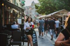СЛАВНЫЙ, ФРАНЦИЯ - 26-ОЕ ИЮНЯ 2017: Официантка девушки носит приказанные напитки во внешнем традиционном ресторане харчевни, пеше стоковые фотографии rf