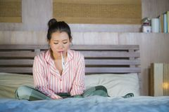 Сладкая азиатская корейская девушка в пижамах предусматриванных с холодом и гриппом одеяла больным страдая принимая температуру с стоковые фотографии rf