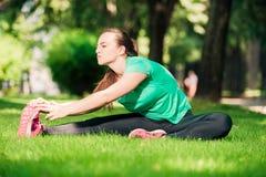 Сладкая молодая женщина протягивая ее ногу на зеленой лужайке стоковое фото rf