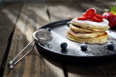 Сладкие блинчики завтрака с клубниками, голубиками и напудренным сахаром стоковое изображение rf