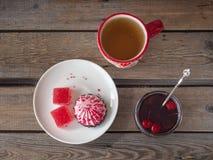 Сладкий обед с мармеладом, зефирами в шоколаде и зеленым чаем в красивой деревенской кружке и опарнике варенья вишни на деревянно стоковое изображение