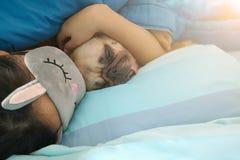 Сладостная азиатская женщина с маской и милой собакой мопса щенка спать r Стоковое фото RF