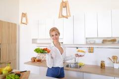 Сладостная женщина держит плиты в руках и проверяет свежесть сваренный Стоковые Изображения RF