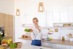 Сладостная женщина держит плиты в руках и проверяет свежесть сваренный Стоковая Фотография