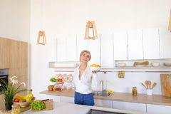 Сладостная женщина держит плиты в руках и проверяет свежесть сваренный Стоковое Изображение RF