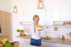 Сладостная женщина держит плиты в руках и проверяет свежесть сваренный Стоковые Фото