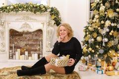 Сладостная женщина усмехается и представляется сидеть на предпосылке рождества стоковое фото