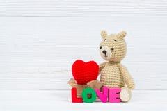 Сладостная кукла плюшевого медвежонка с текстом влюбленности и красным вязать сердцем дальше Стоковые Изображения RF