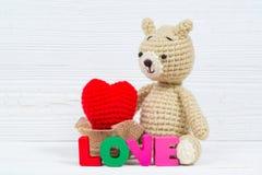 Сладостная кукла плюшевого медвежонка с текстом влюбленности и красным вязать сердцем дальше Стоковые Фото