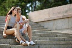 Сладостная пара красивой девушки с привлекательными товарищескими посадочными местами на шагах на естественную запачканную предпо Стоковая Фотография RF