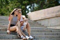Сладостная пара красивой девушки с привлекательными товарищескими посадочными местами на шагах на естественную запачканную предпо Стоковое Изображение RF