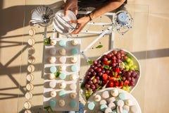 Сладостная таблица свадьбы с тортами и клубникой, виноградинами на верхней части, приносить Стоковая Фотография RF