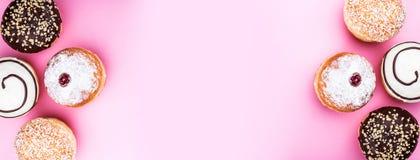 Сладостные и свежие донуты при порошок сливк, кокоса и сахара шоколада изолированный на розовой предпосылке стоковое изображение