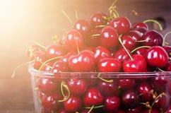 Сладостные красные вишни в стеклянном шаре на темном деревянном backgound с космосом экземпляра Солнечное лето и концепция сбора  Стоковые Изображения
