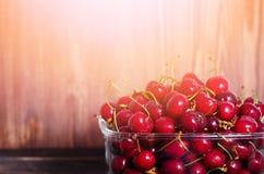 Сладостные красные вишни в стеклянном шаре на темном деревянном backgound с космосом экземпляра Солнечное лето и концепция сбора  Стоковое Изображение RF