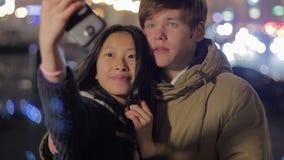 Сладостные пары подростков принимая фото на smartphone, социальной сети, selfie видеоматериал