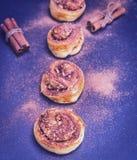 Сладостные плюшки с циннамоном и грецкими орехами на черной предпосылке Стоковое Фото