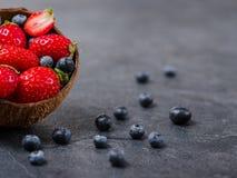Сладостные свежие клубники и голубики в шаре на темной предпосылке оливка масла кухни еды принципиальной схемы шеф-повара свежая  стоковое изображение