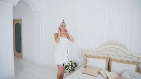 Сладостный дама Приходить из ливня, положения и представлять в полотенце около кровати против Стоковая Фотография