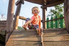 Сладостный ребёнок на деревянной спортивной площадке для детей стоковое изображение