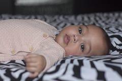 Сладостный ребёнок на кровати смотря в камере стоковое фото rf