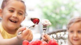 2 сладостных девушки в ресторане едят красные клубники с crea Стоковое Фото